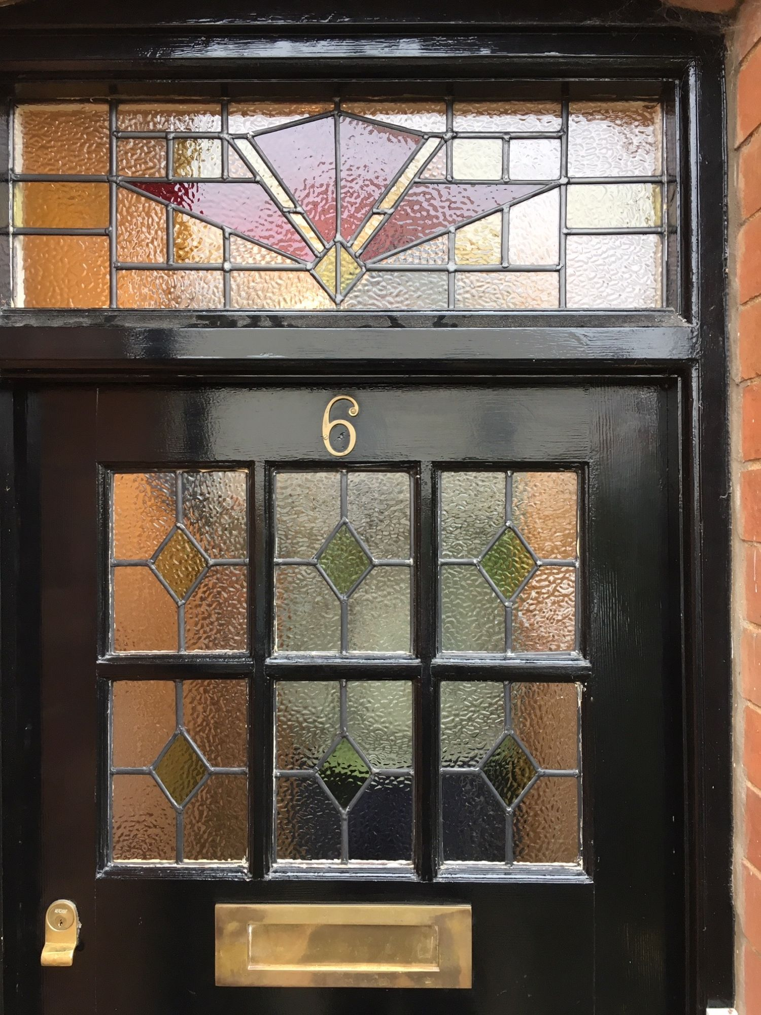 Black front door with stained glass panels
