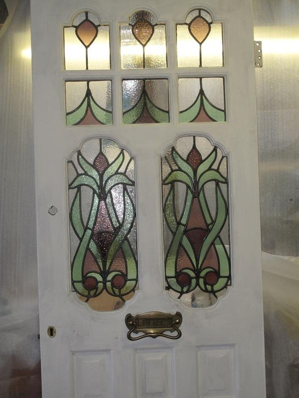 white front door with stained glass panels in green and purple