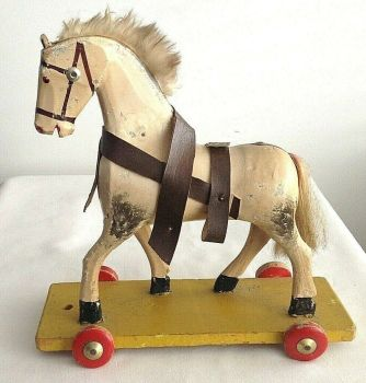 Antique or vintage carved painted wooden toy horse on wheels
