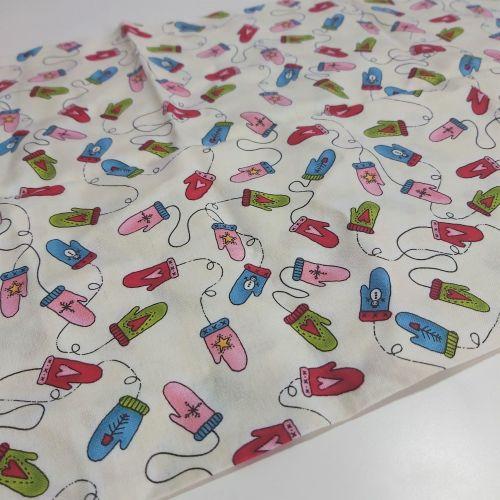 Mittens on cream cotton fabric