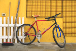 coloured photo of bright red bike against yellow wall - Tent fold card