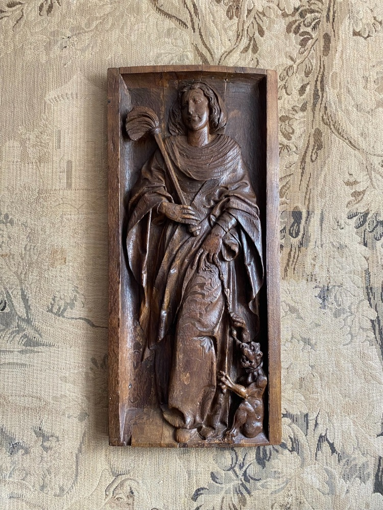 A 16th Century Carved Oak Panel Of St.Juliana With The Chained Devil At Her