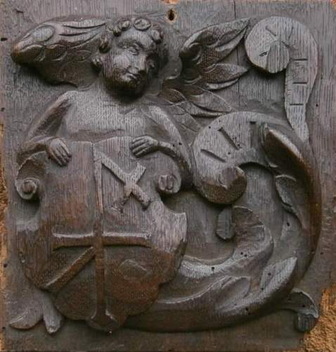 A 16th century English oak panel depicting an angel holding a shield with m