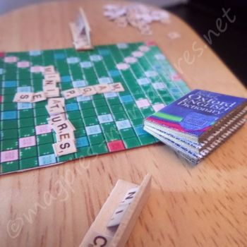 Scrabble board game, dictionary and racks.