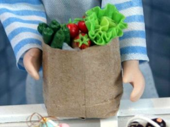 Lettuce and veg in brown paper shopping bag.