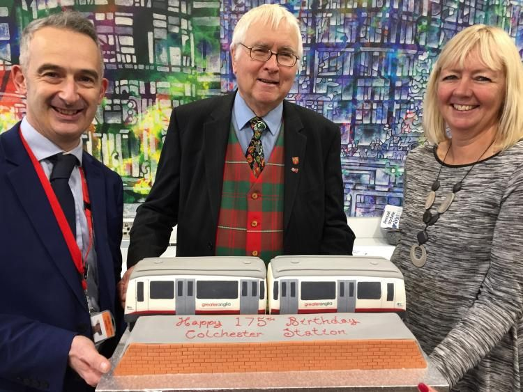 Dignitaries posing with 175th anniversary train shaped birthday cake