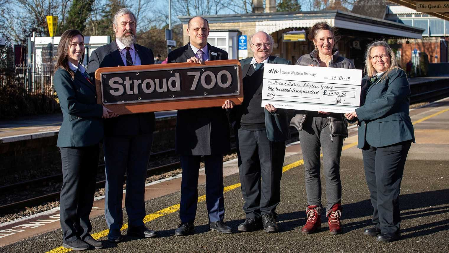 Dignitaries pose for photograph with Stroud 700 nameplate and cheque