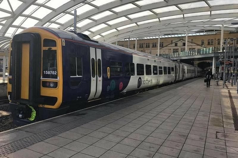 Northern Class 158 stands at a railway station