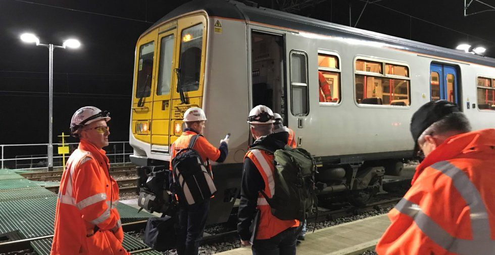 Engineers stand around a Class 319 EMU