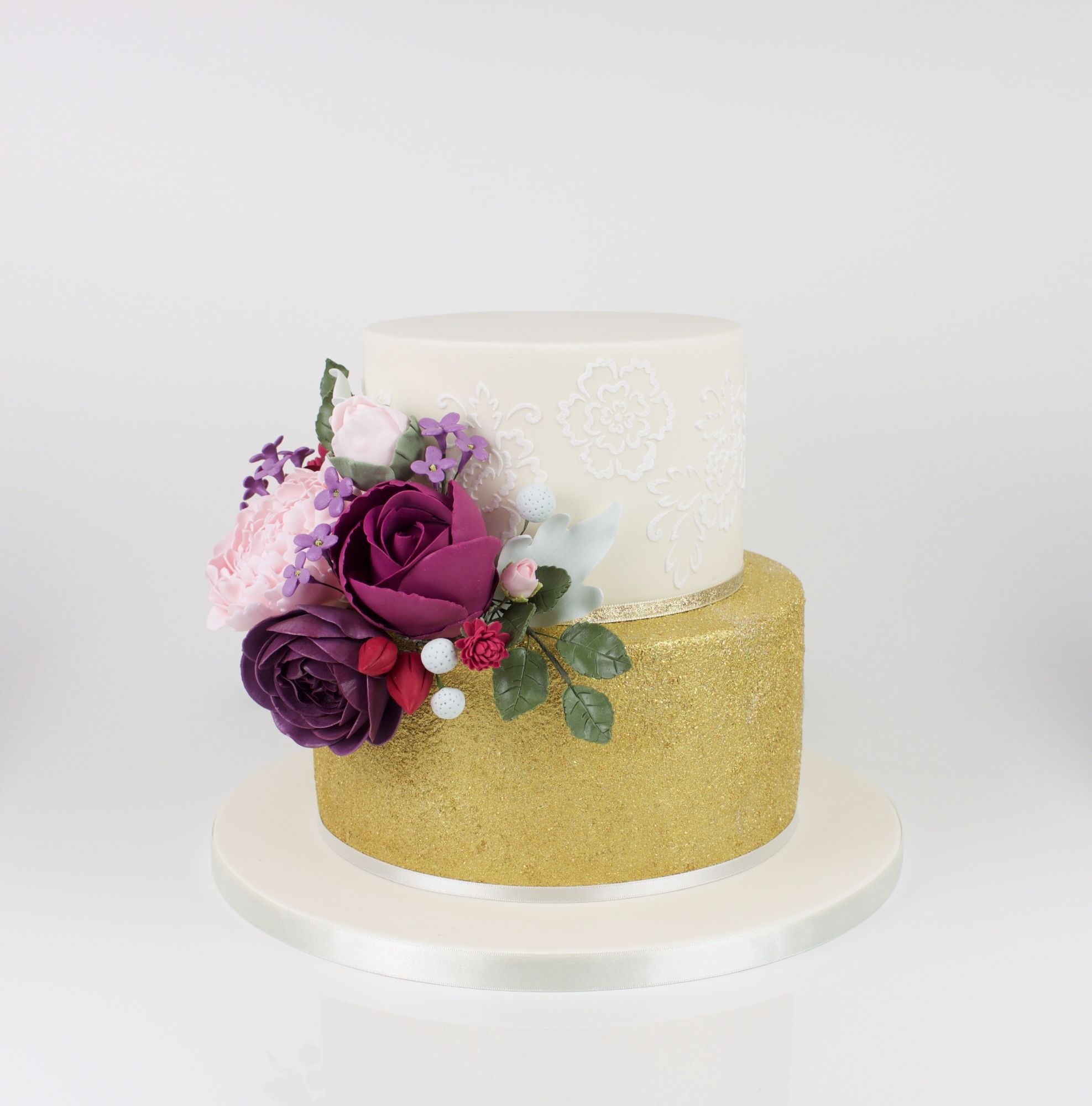 2 tiers gold glitter cake with brush embroidery and dark purples and pinks flowers