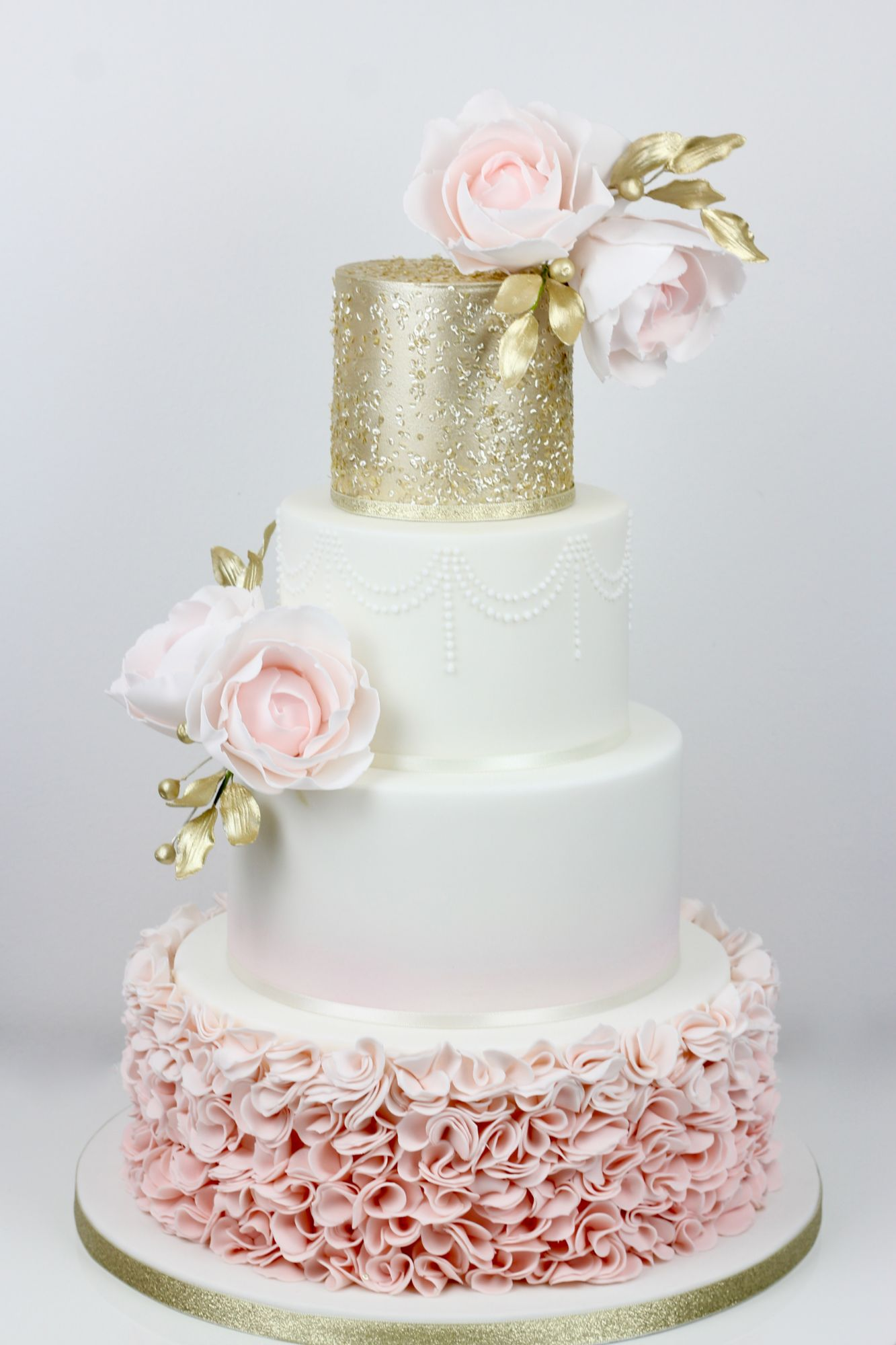 4 tiers with pink ombre icing ruffles with airbrushed ombre effect top tier gold sequins with pink roses and handpainted gold leaves