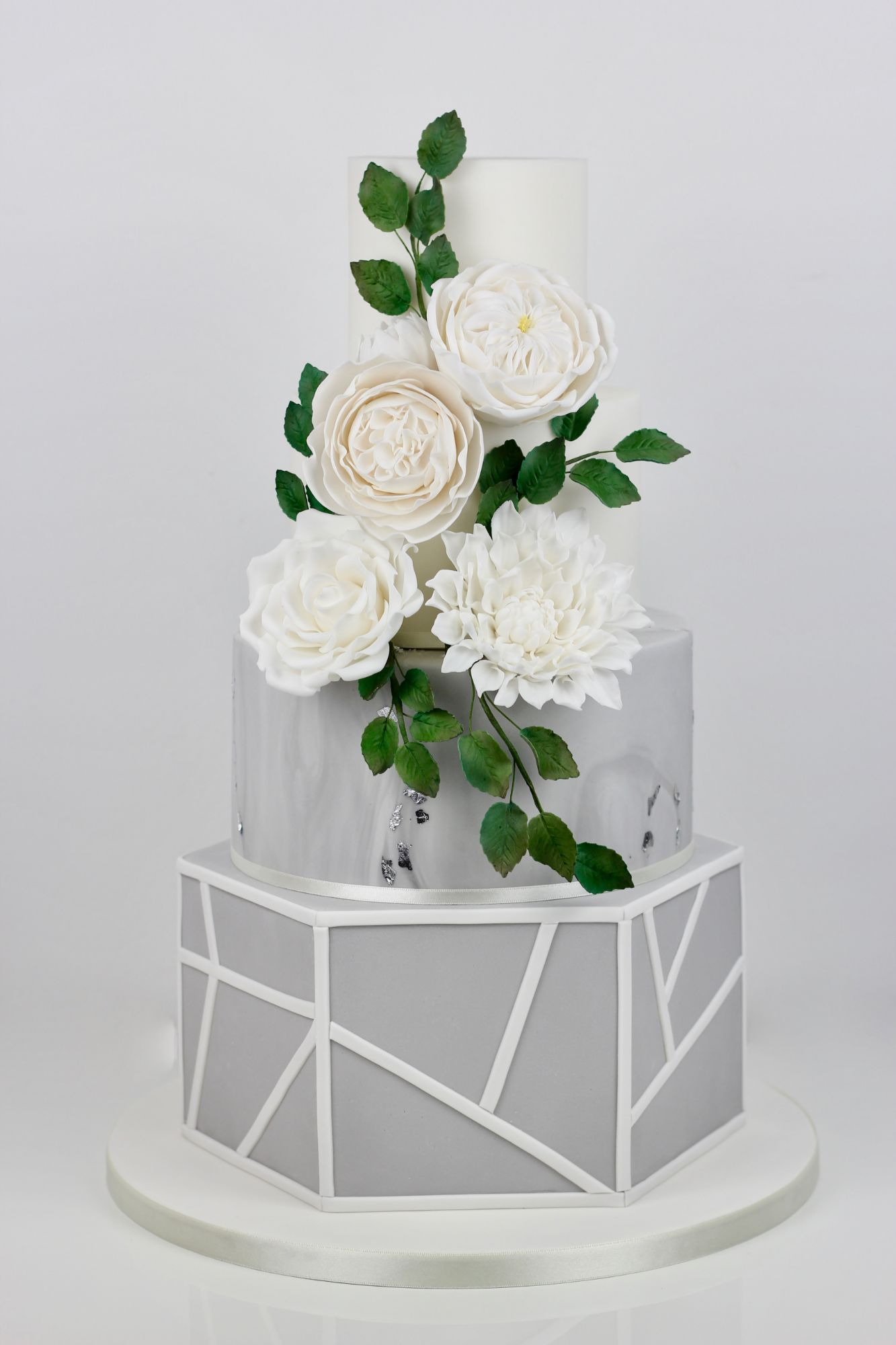 Hexagon, marble wedding cake with lots of  flowers and greenery