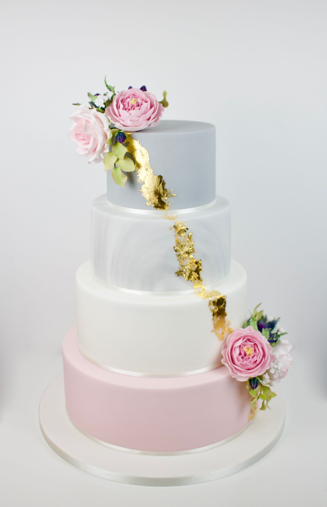 4 teir pale pink amd grey marble wedding cake with gold leaf and pink sugar flowers.