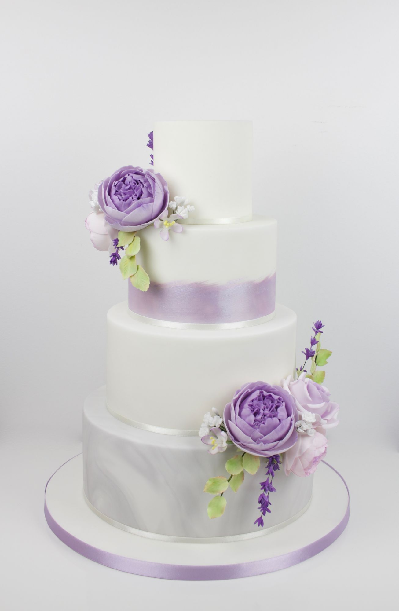 Lurstered purple wedding cake with sugar peonies and a marble tier.