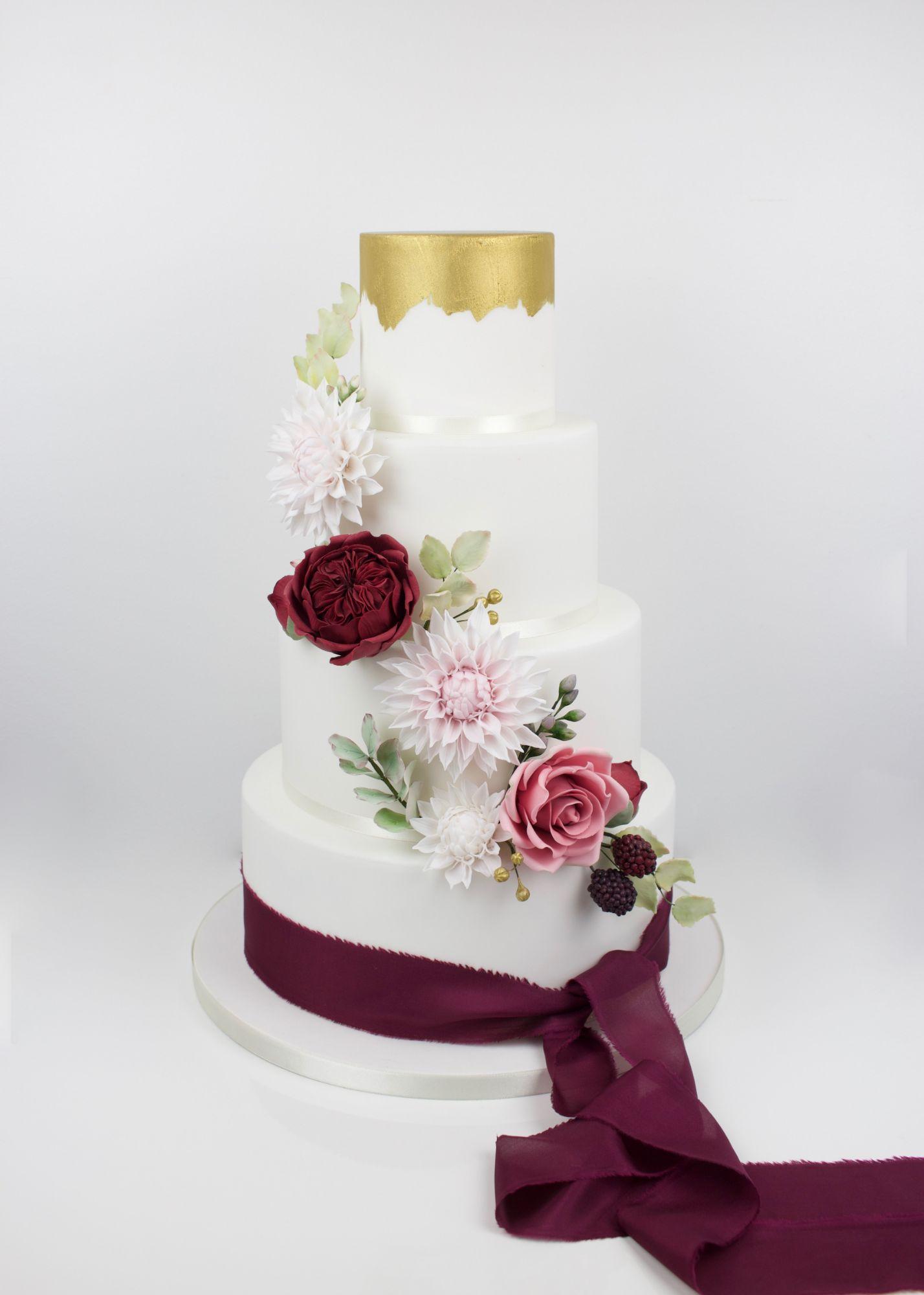 Handpainted gold wedding cake with casscadding sugar david austin roses, dalias and eucalyptus leaves.