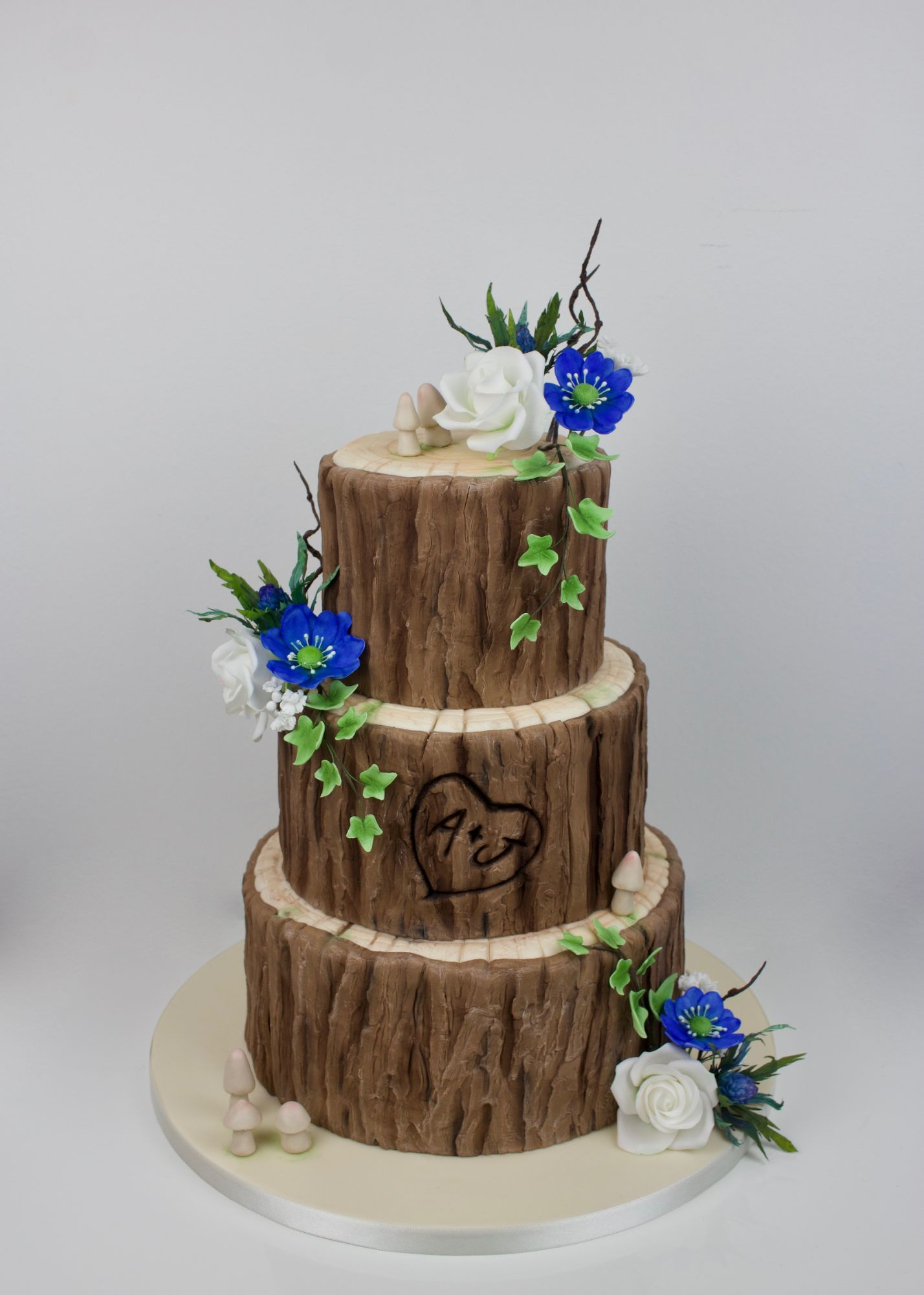 cake made to look like a tree trunk with scottish wild flowers, ivy and mushrooms