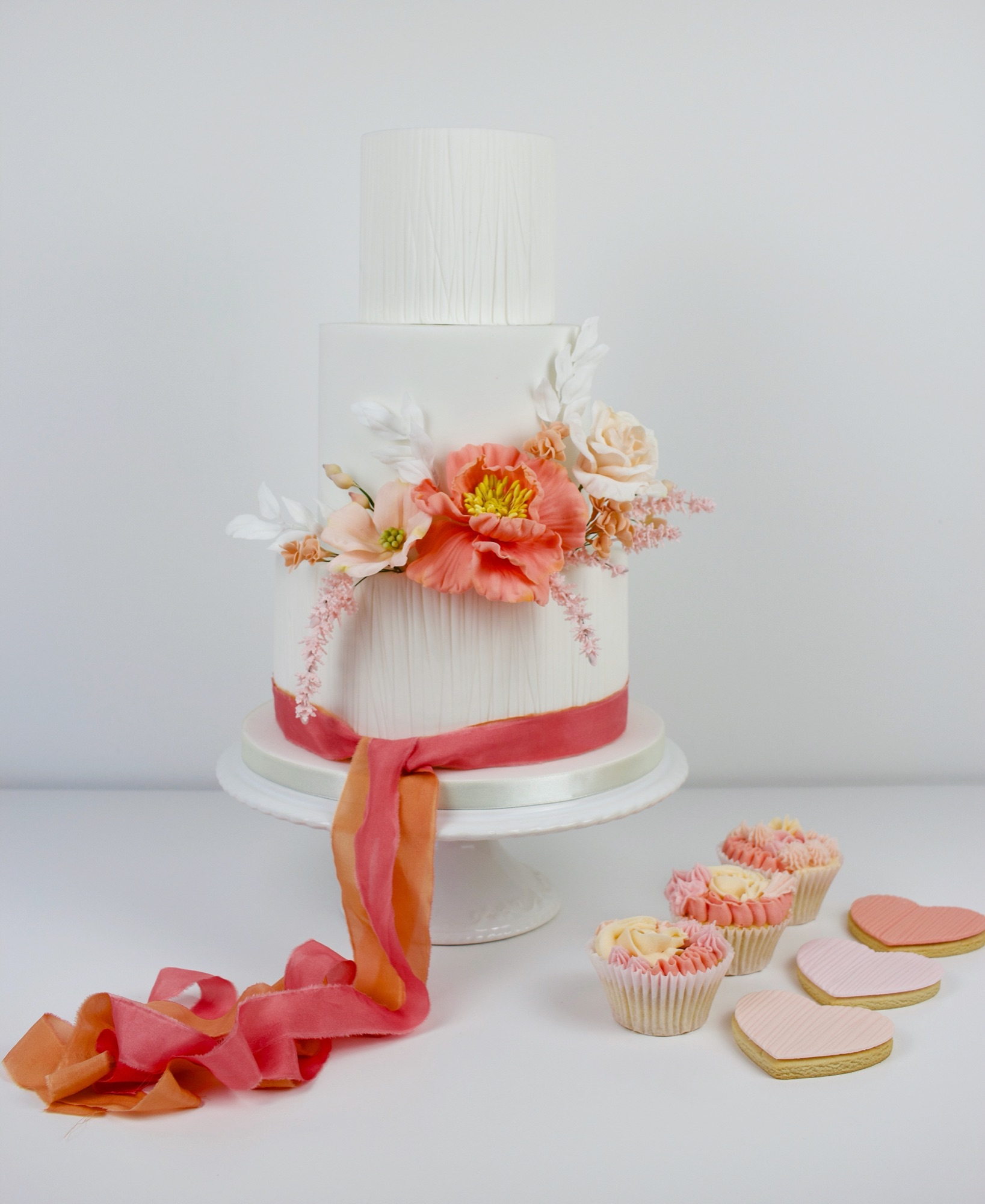 Testured wedding cake, with coral & pink flowers.