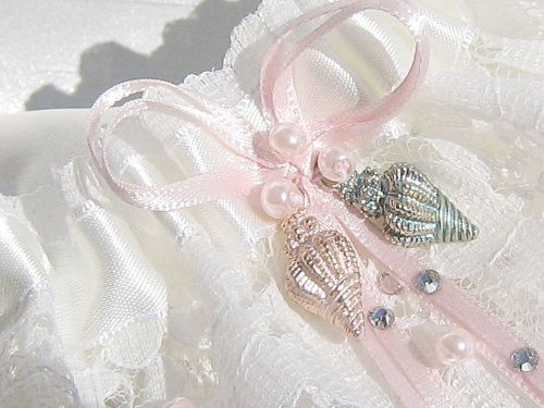 Lace Wedding Garter With shells on the front and ribbon bows in a blush pink colour.
