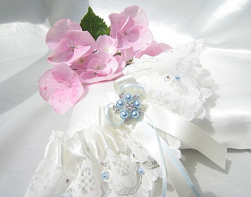 picture of a bridal garter with stitched on Swarovski pearls and crystals, with bows.