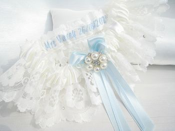 A lace wedding garter which has been personalised on the inside of the garter, with tied ribbon blue bows.
