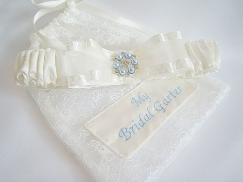 Wedding Garter & Dust Bag Which Has Been Personalised In A Dusty Blue Embroidery Thread.