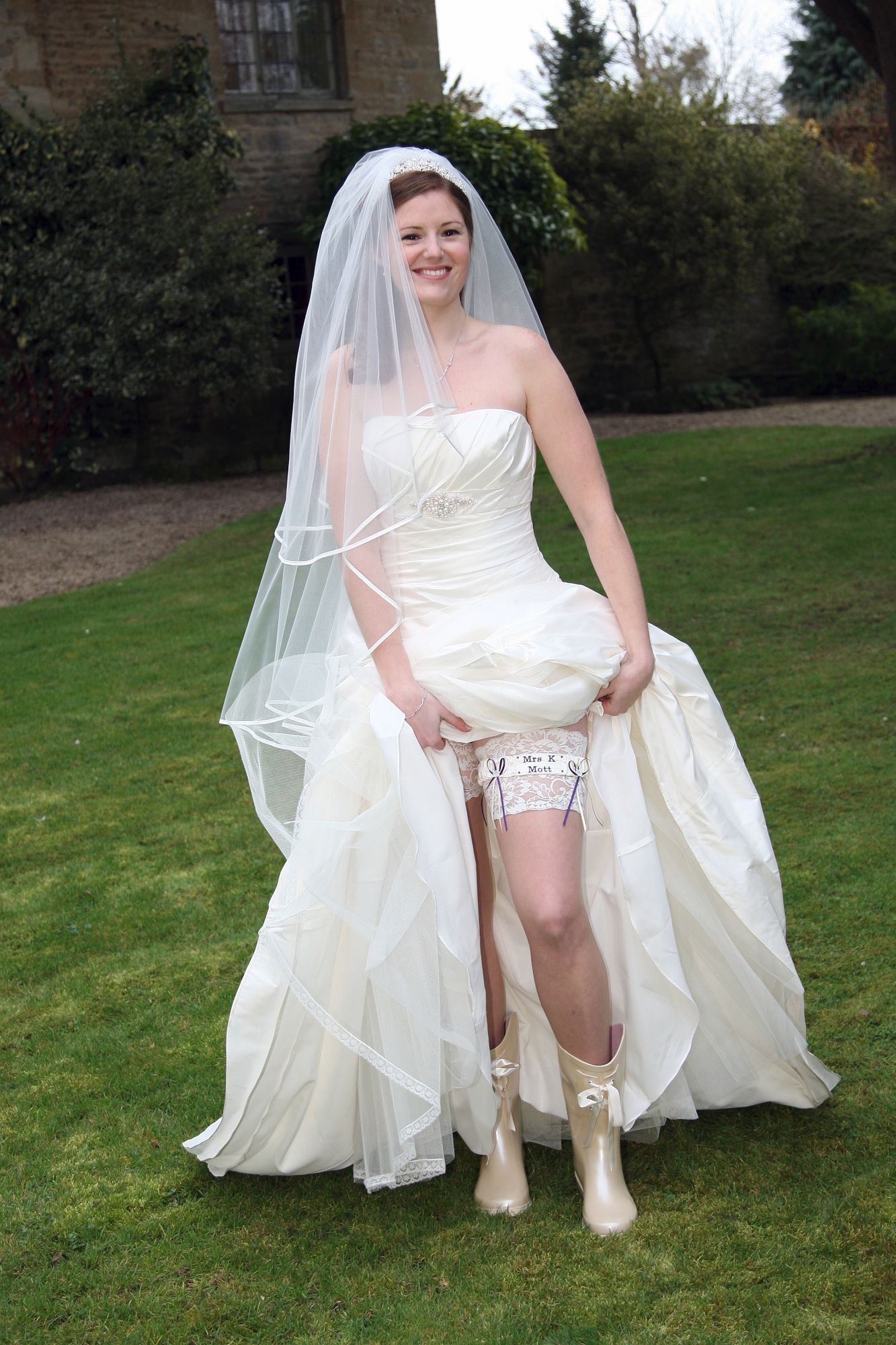 Bride showing off her bridal garter and wedding wellington boots.