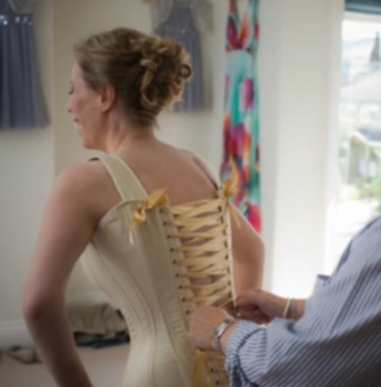 girl being laced into a bridal corset