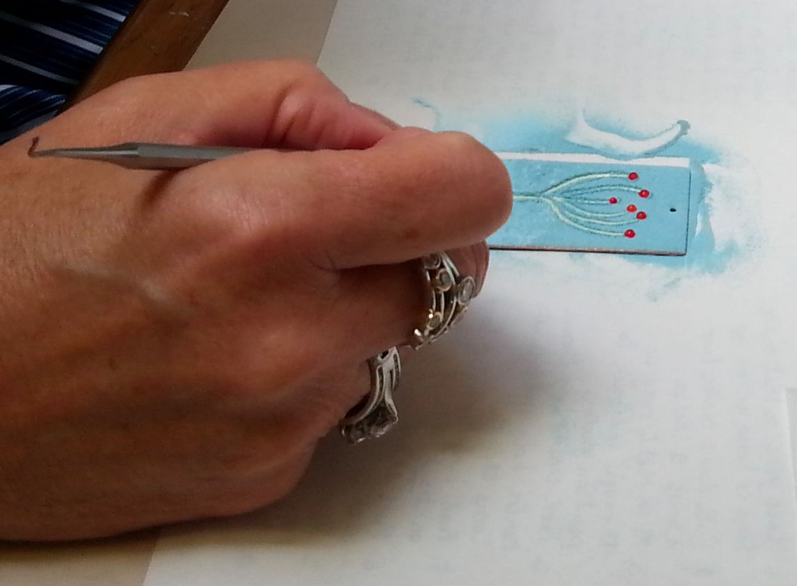 A student creates a design at enamelling session