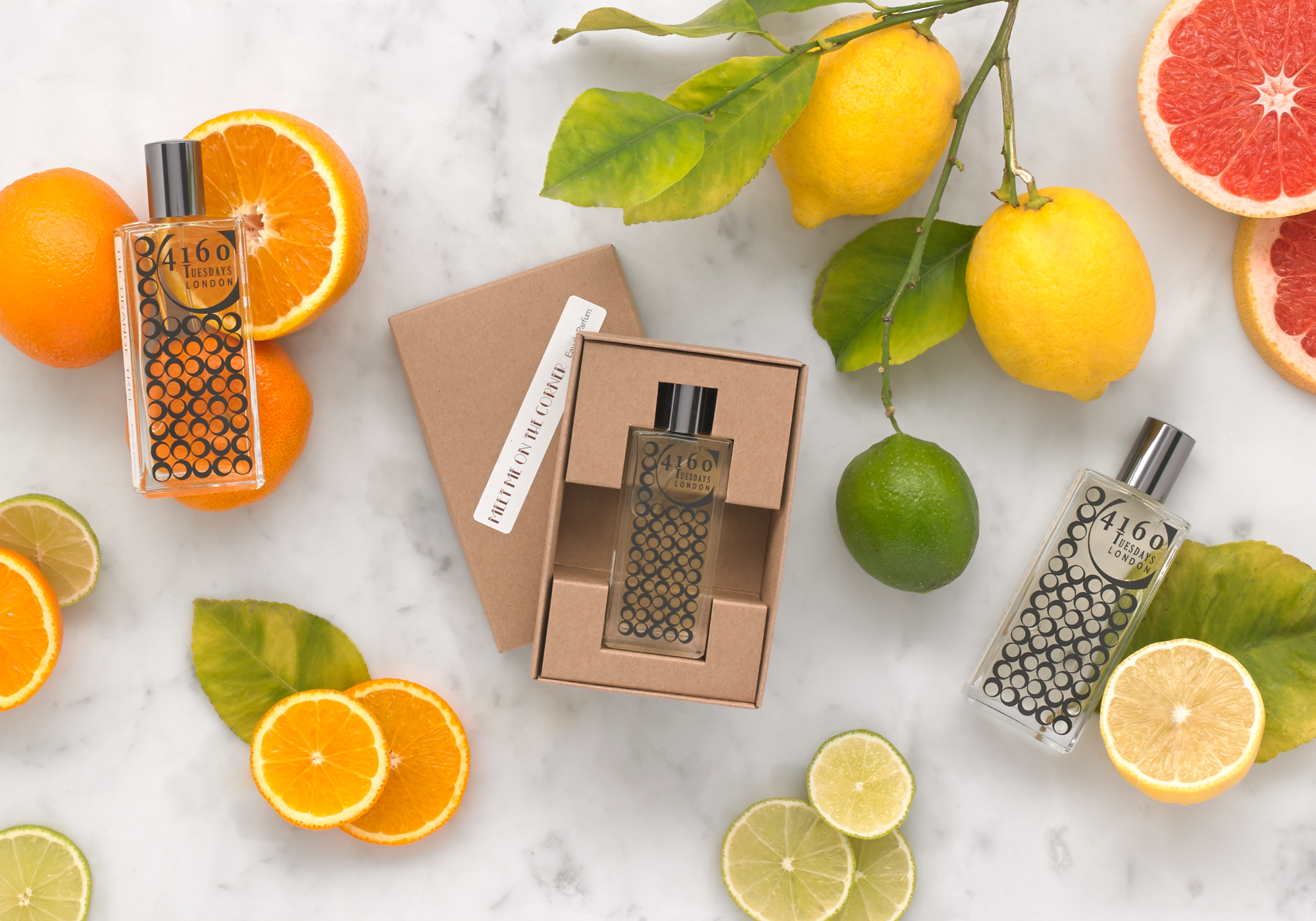 Stylised photo of a bottle of 4160 Tuesdays perfume surrounded by oranges, lemons and limes