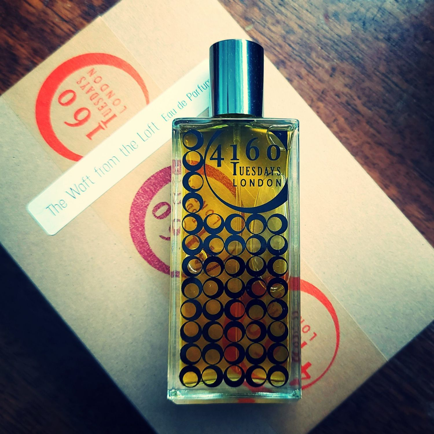 A bottle of 4160 Tuesdays perfume on top of it's box