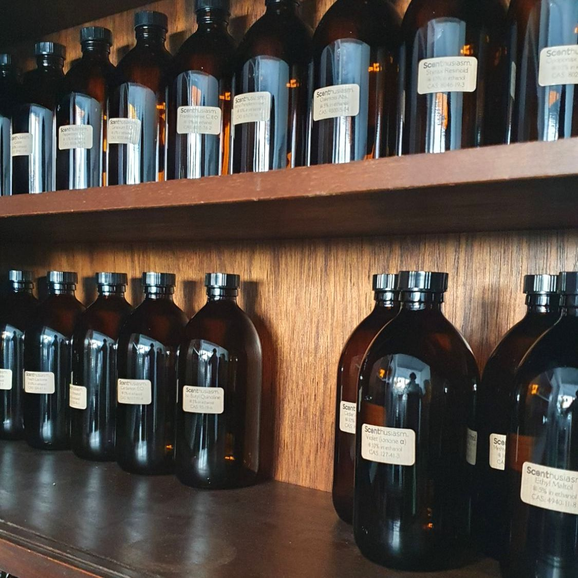 A shelf containing a number of dark brown bottles