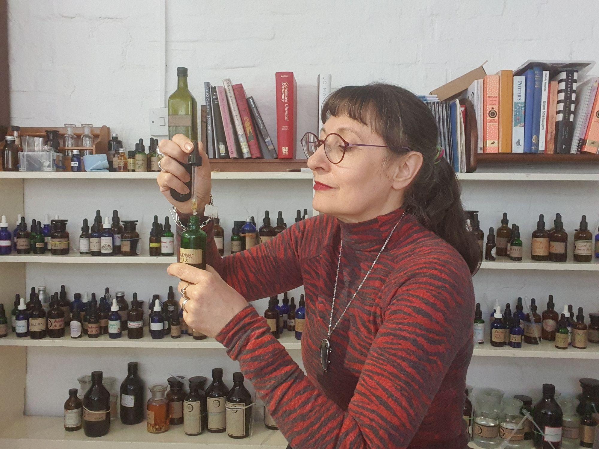 Perfumer Sarah McCartney in front of a shelf full of perfume materials