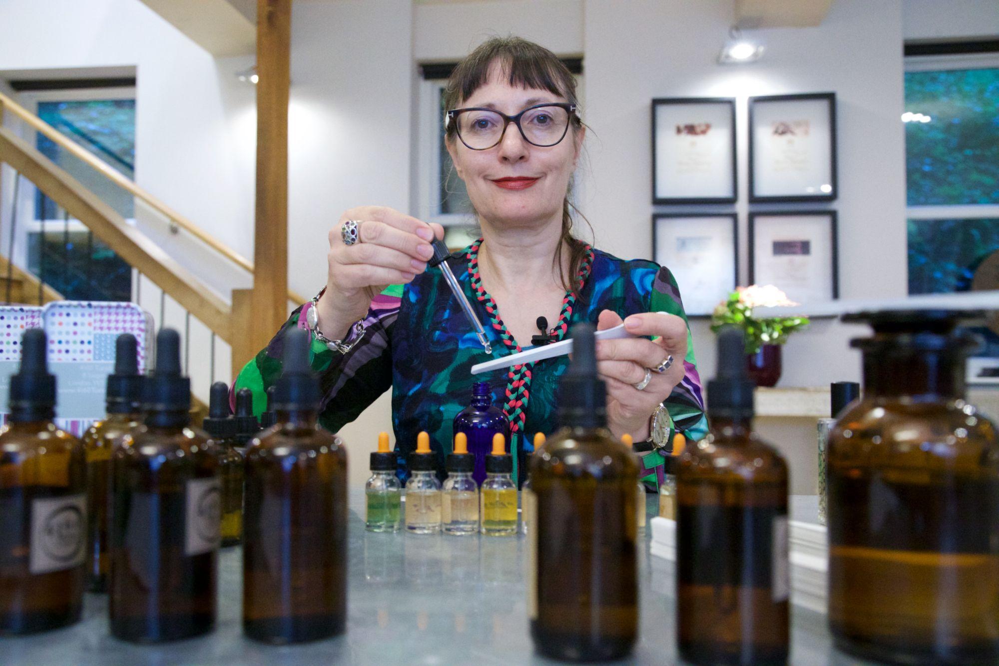 Perfumer Sarah McCartney posing with bottles of perfume materials