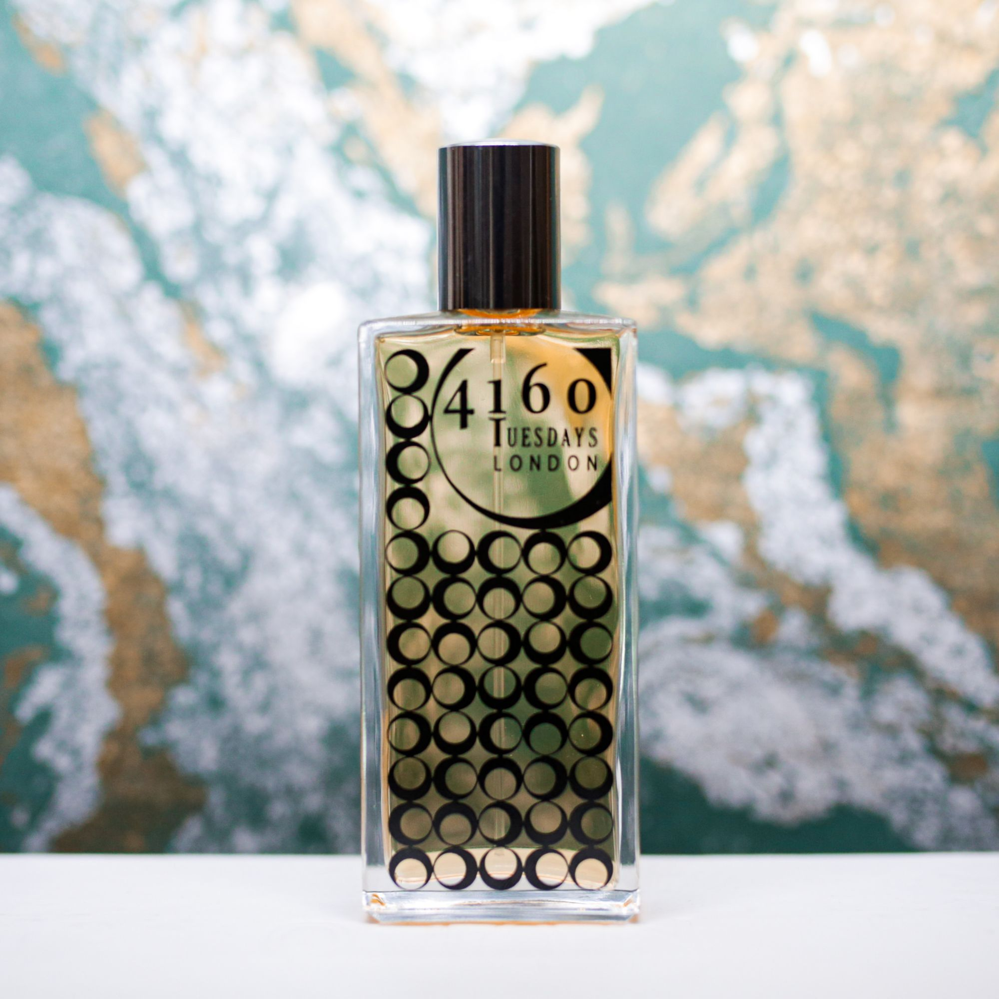 A bottle 4160 Tuesdays perfume against a dark green, silver and gold marbled backdrop