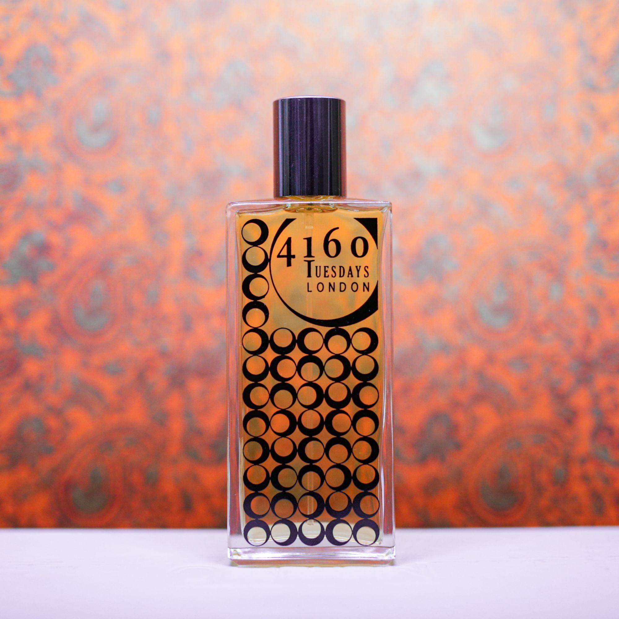 A bottle of 4160 Tuesdays Perfume against a metallic orange backdrop