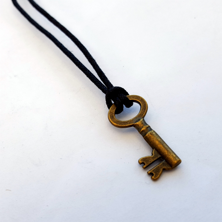 Small bronze key on black cord necklace MN029