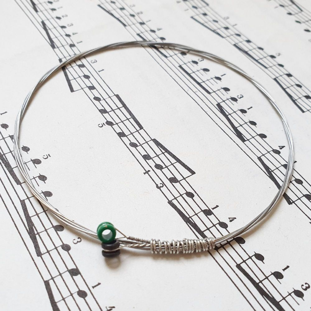 Guitar string bracelet with  black and green ball ends GSB025
