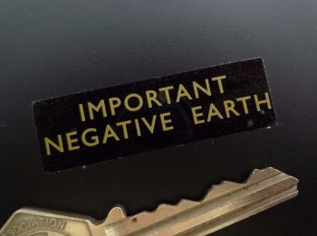 "Negative Earth Gold on Clear Sticker. 1.75""."