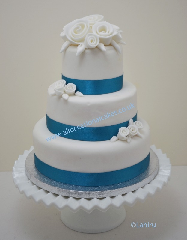 ocean blue colour ribbon with white roses wedding cake 3 tier from £ 165, bristol wedding cakes, cakes pictures, magic wedding cakes,  uk cakes, uk wedding cakes, emersons green wedding cakes, cheap cakes, best cakes, international wedding cakes, international cakes, egg free cakes, egg less cakes, downend cakes, king cakes, downend wedding cakes, colourful cakes, all occasional cakes, cakes for all occasions, tasty wedding cakes, golden wedding cakes, sweet wedding cakes, anniversary cakes, sri lankan wedding,  wedding cakes, england wedding cakes, england cakes, birthday cakes, google cakes, winter cakes, snow cakes, topsy turvy cakes, cascade, cheap cakes, cheap wedding cakes, special wedding cakes, best cakes, uk, cakes, cake, cake makers, weddings, wedding, bristol, bristoluk, bath, bathuk, novelty cake, novelty cakes, unique cake, unique cakes, custom cake, custom cakes, birthday cake, birthday cakes, wedding cake, wedding cakes, corporate cake, corporate cakes, winning wedding cakes, winning cakes, yate wedding cakes, filton wedding cakes, clifton wedding cakes, winterbourne wedding cakes, London wedding cakes, royal wedding cakes, bristol wedding cakes, wedding cakes Bristol, wedding cake Bristol, Asian wedding cakes, indian wedding cakes, expensive cakes, expensive wedding cakes, rich wedding cakes, royal wedding cakes, rich cakes, gold wedding cakes, 24k wedding cakes, tasty wedding cakes, royal wedding cakes, queen wedding cakes, queen birthday cake, king's wedding cakes, Kings birthday cakes, prince wedding cakes, prince birthday cakes, best cakes, love cake, magic cakes, cake, fairy cakes, hot cakes, cupcakes, cupcake cakes, fondant cakes, cupcakes, my ace cakes of uk, cakes Sri Lanka, fab cakes, cakes sri lanka, south Gloucestershire, cake decoration, catering for weddings, Lahiru Peiris,