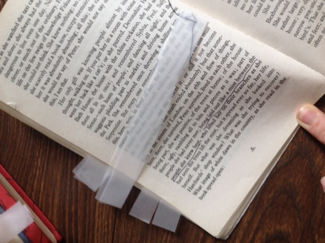 Page of a book with a strip of tracing paper stiched in the page visible.