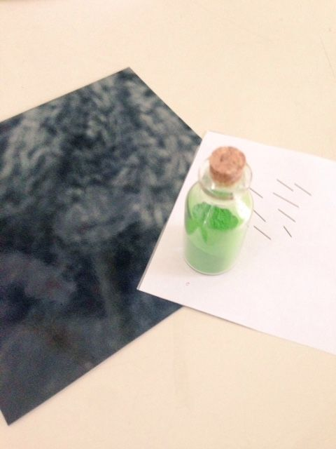 Glass bottle containing green poweder, reating on a paper note with aabdtract shapes in black and white