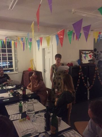 People sitting around a table and eating food. Bunting is hanging from the ceiling. A white woman with short hair, dressed in a green dress, is standing and reading from a paper.