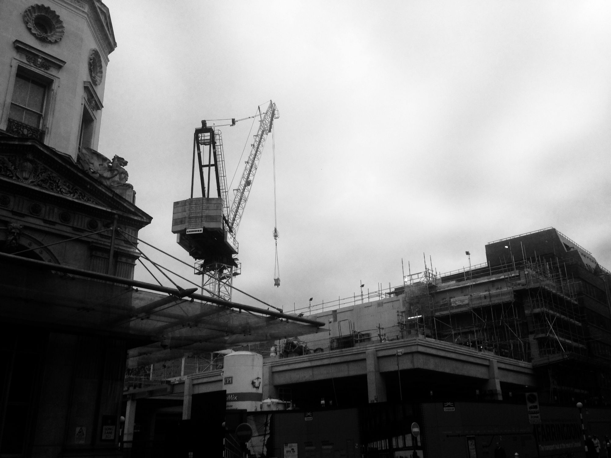 Black and white image of a crane and a building site.