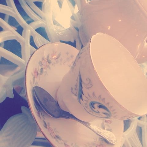 Faded colour image of a teacup and saucer with delicate floser pattern