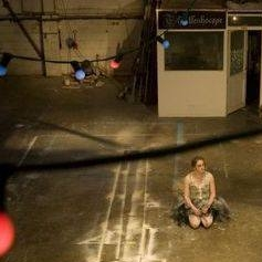 A woman in ballerina outfit sits on the floor of an industrial space