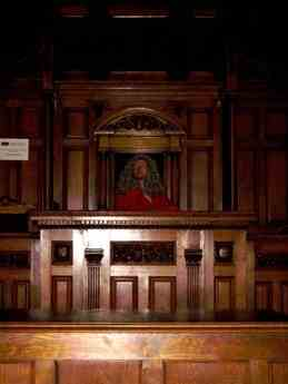 Dimly lit coourtroom, a figure in a judges wig sitting behind a wooden table.