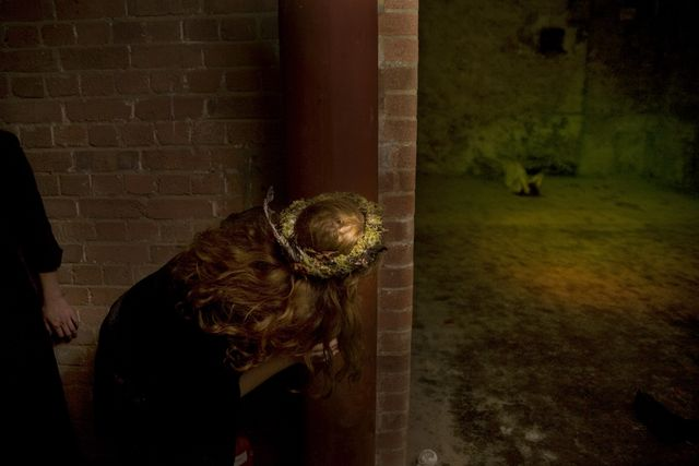 Brick building, dimly lit. A woman with long blond hair is crouching on the floor, pearing around a corner.
