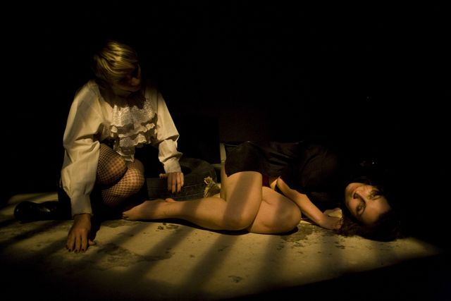 Two woman, one crouching in a dimly lit room ching, one  lying on the floor