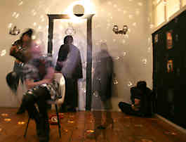 A room with a disco ball with several people standing and a person sitting  hunched over in the corner.
