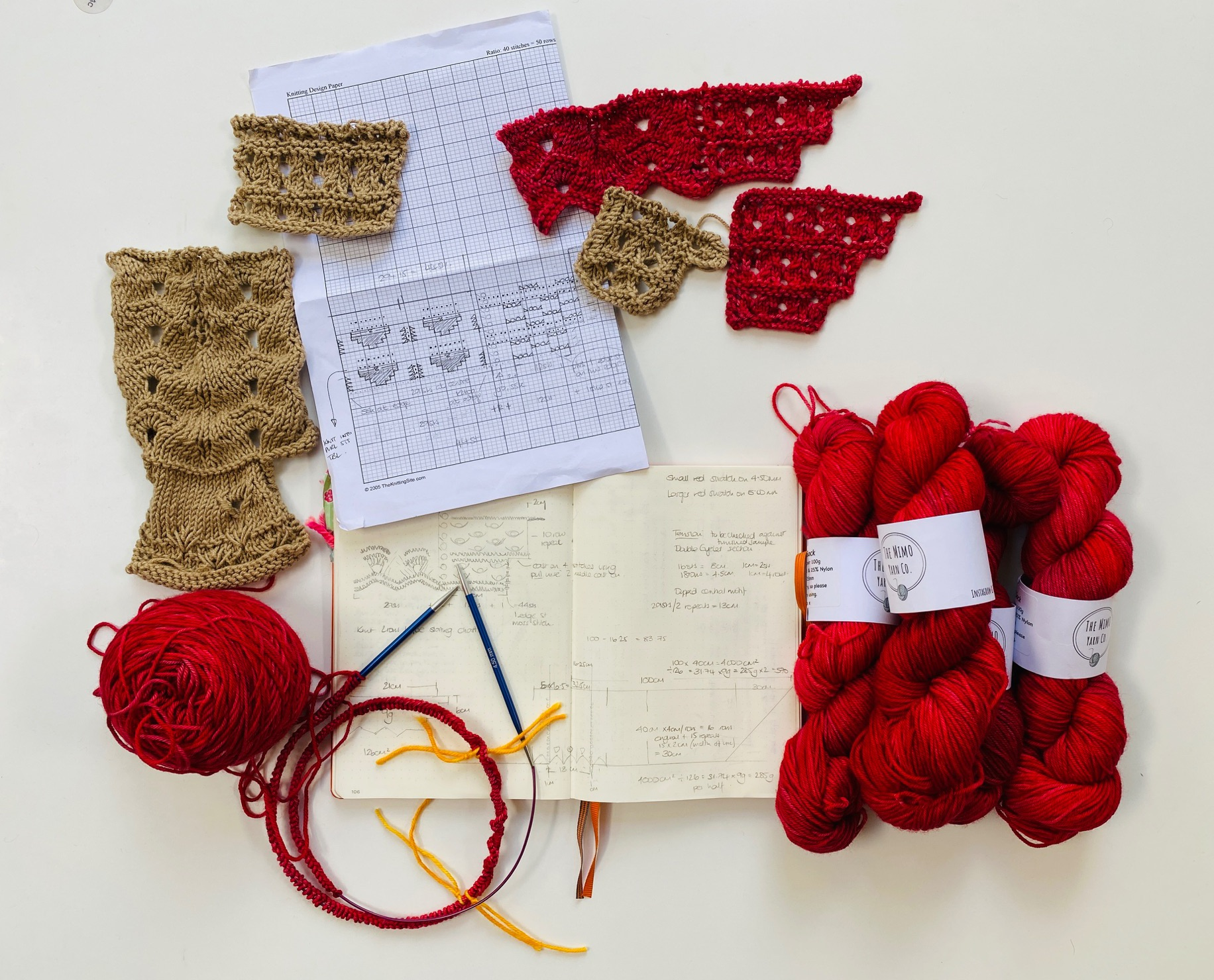 selcetion of knitted samples  and skeins of rad yarn lay beside an open skecthbook and graph paper with a circular knitting needle on a white bacgrounf